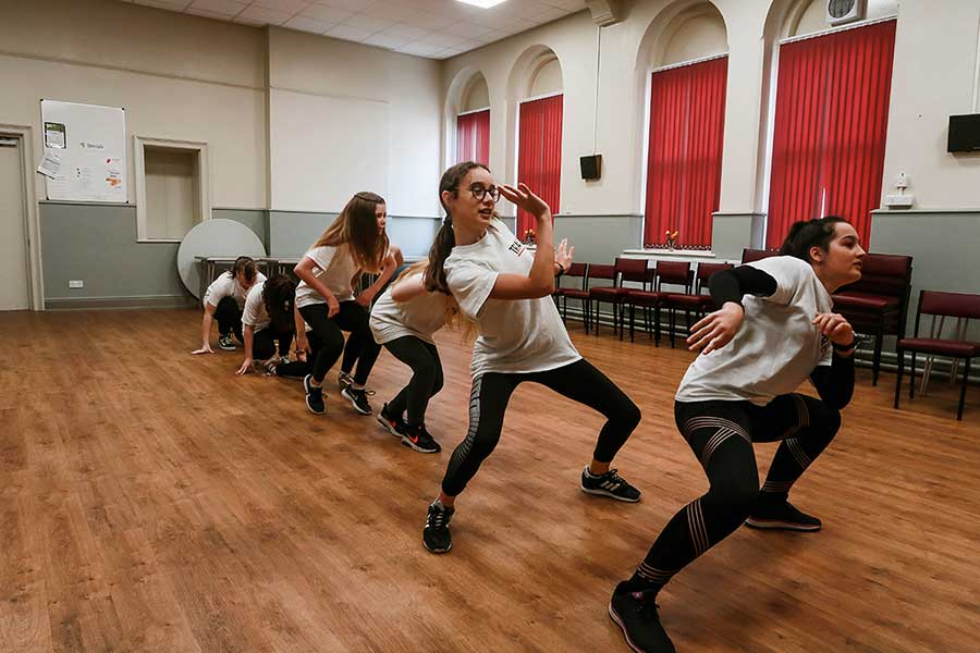 a line of young people in white t-shirt and blacks sports leggings street dancing in a hall