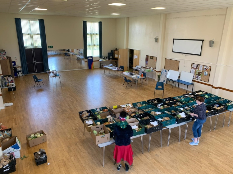 a picture of a hall from high up looking down on long tables of food with people preparing food packages