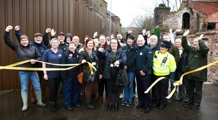 a lot of people at Middleport Matters cutting a ribbon with their hands in the air
